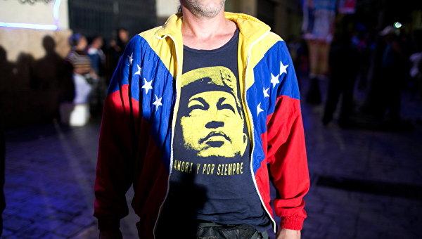 Сторонник правящей партии Венесуэлы с портретом Уго Чавеса, архивное фото