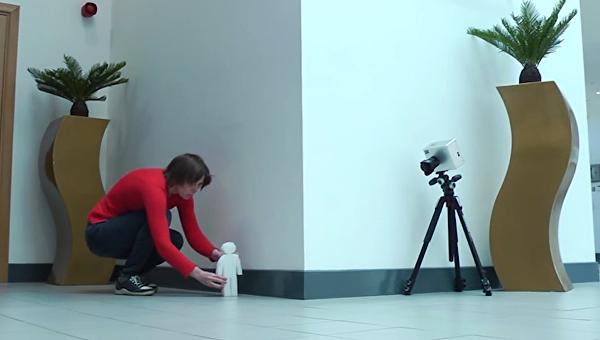 Ученый устанавливает человечка, за которым будет следить камера (справа)
