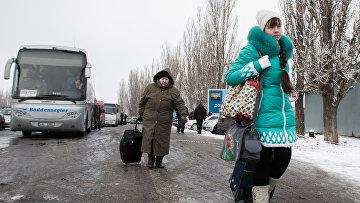 Пожилая женщина с девочкой у пропускного пункта в Донецкой области на границе Украины с Россией. Архивное фото