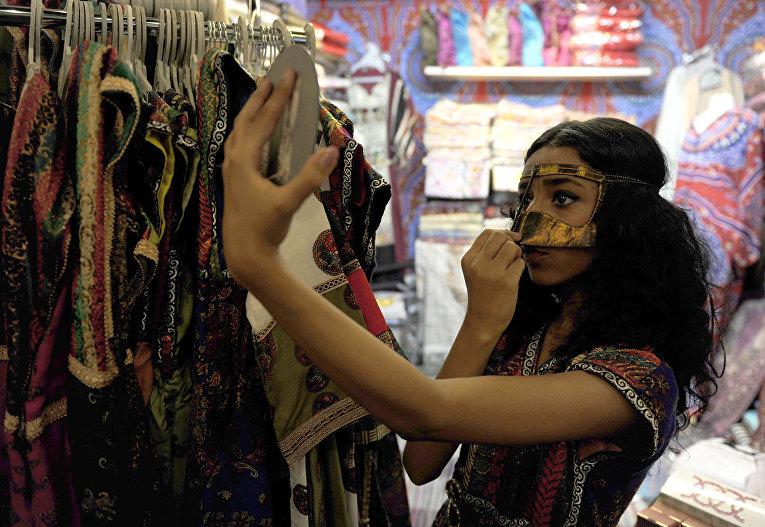 Саудовская девушка примеряет маску в магазине