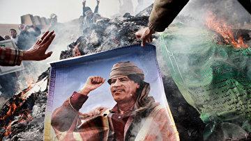 Жители Бенгази сжигают портреты Муамара Каддафи, плакаты с его цитатами и Зеленую книгу Каддафи. Архивное фото