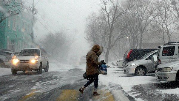 Прохожий на Комсомольской улице во время снежного циклона во Владивостоке