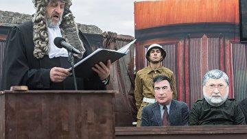 Актеры в масках Игоря Коломойского и Михаила Саакашвили (справа налево) во время перформанса Процесс