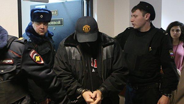 Сотрудники полиции ведут Александра Величко, подозреваемого в убийстве директора компании Мон-компани