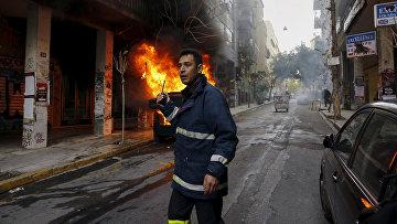 Сотрудник пожарной безопасности вызывает подкрепление во время столкновений и протестов в центре Афин, Греция. Февраль 2016