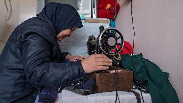 Женщина штопает одежду в лагере беженцев, размещенном в здании одной из школ Дамаска