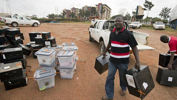 Работник избирательной комиссии несет коробки с бюллетенями в центр подсчета в Кампале, Уганда. Архивное фото
