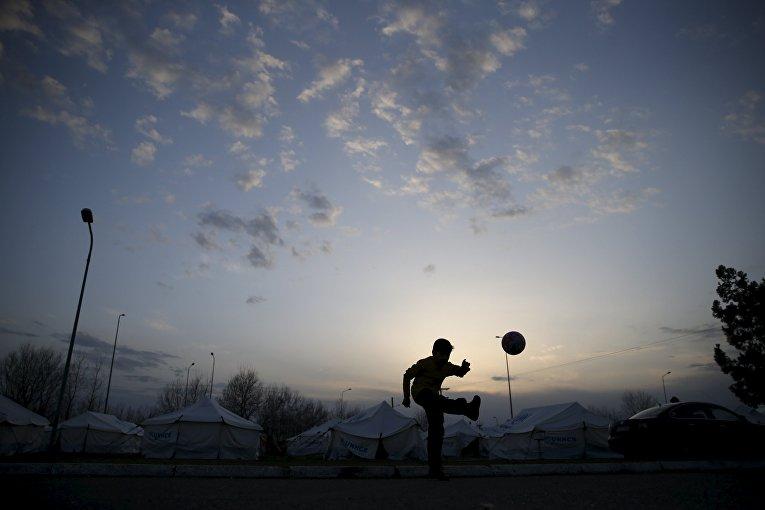 Ребенок-мигрант играет в мяч в поселке Поликастро, Греция. 23 февраля 2016