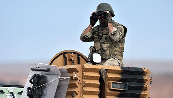 Турецкий солдат наблюдает в бинокль на турецко-сирийский границе. Архивное фото