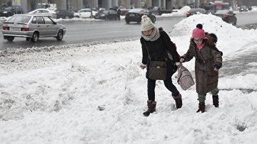 Пешеходу идут по глубокому снегу на одной из улиц Москвы после сильного снегопада