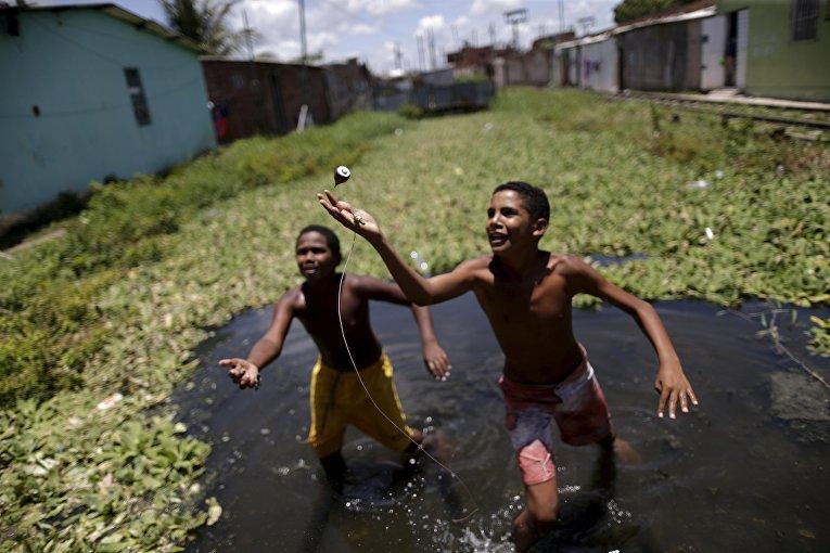 Дети играют в воде в трущобах Ресифе, Бразилия. 2 марта 2016