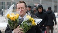 Мужчина с букетами цветов в преддверии праздника 8 марта в Москве
