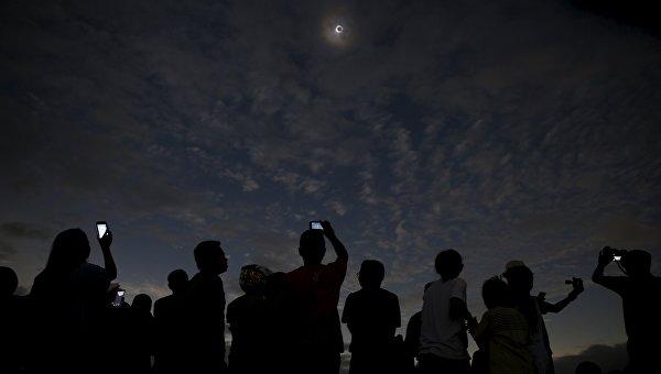 Люди наблюдают за солнечным затмением в Индонезии, 9 марта 2016