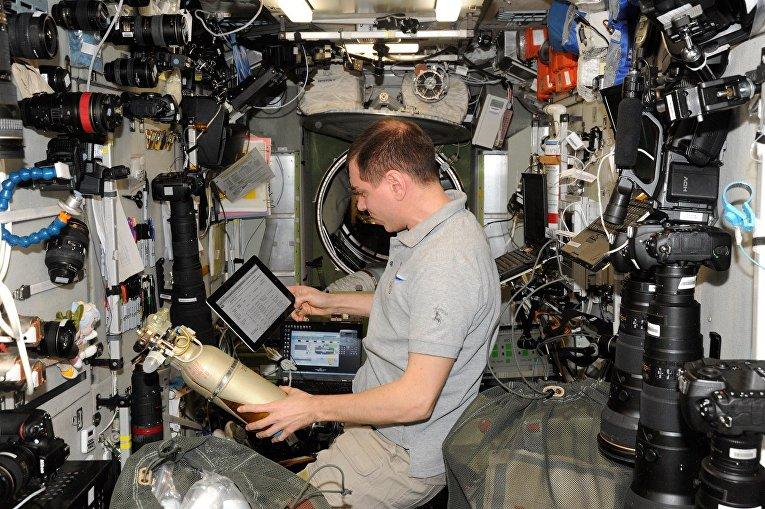 Космонавт Сергей Волков с кислородными баллонами на МКС