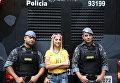 Участница демонстрации фотографируется с полицейскими в городе Сан-Паулу, Бразилия