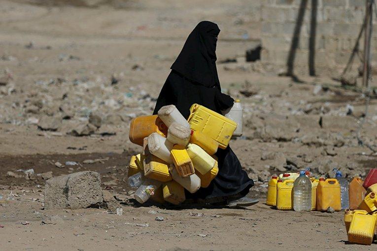Женщина с канистрами идет за питьевой водой в городе Сана, Йемен