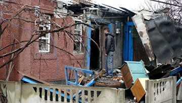 Мужчина у дома, поврежденного в результате обстрела украинскими силовиками, в Макеевке