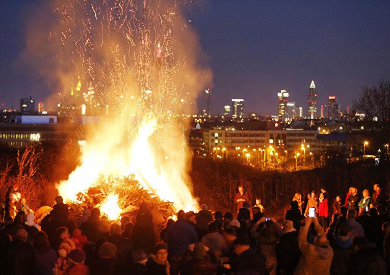 Люди собираются вокруг пасхального костра в пригороде Франкфурта, Германия