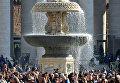 Верующие возле фонтана на площади Святого Петра перед началом мессы в Пасхальное воскресенье, Ватикан