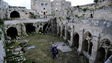 Сирийские архитекторы осматривают разрушенную боевиками крепость Крак де Шевалье в провинции Хомс