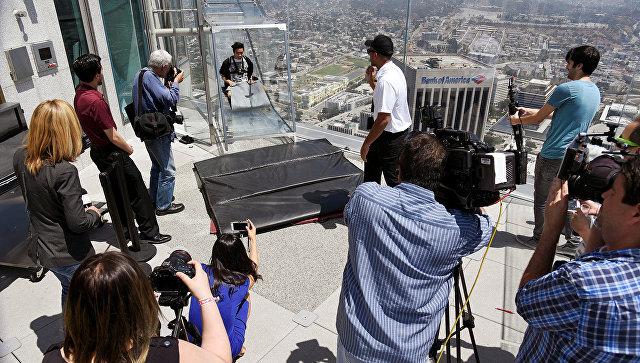 Представитель СМИ во время презентации Skyslide на внешней стороне Bank Tower в Лос-Анджелесе, США. Июнь 2016