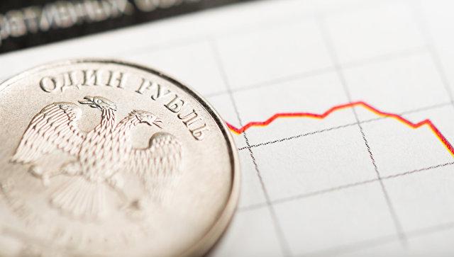 Монета в один рубль на фоне графика. Архивное фото