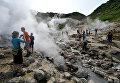 Туристы осматривают долину гейзеров на одном из склонов Мутновского вулкана