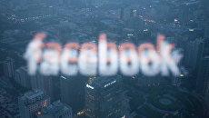 Логотип социальной сети Facebook в отражении экрана монитора компьютера в окне/ Архивное фото
