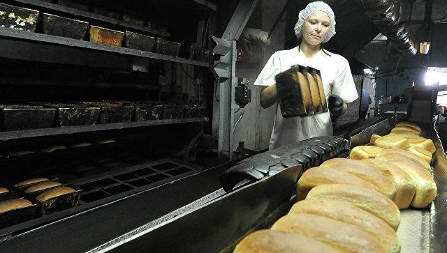 Работница вынимает из формы готовый хлеб. Архивное фото