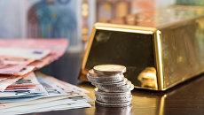 Слиток золота, монеты и банкноты евро