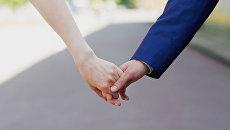 Влюбленные держатся за руки. Архивное фото