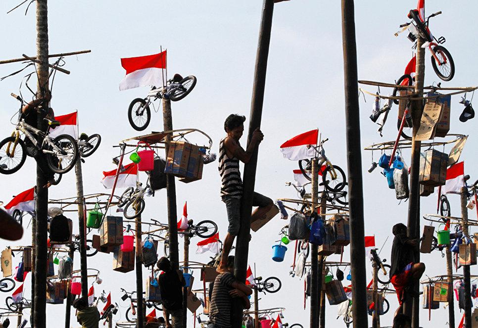 Участники игры Panjat Pinang, которая устраивается на День независимости Индонезии