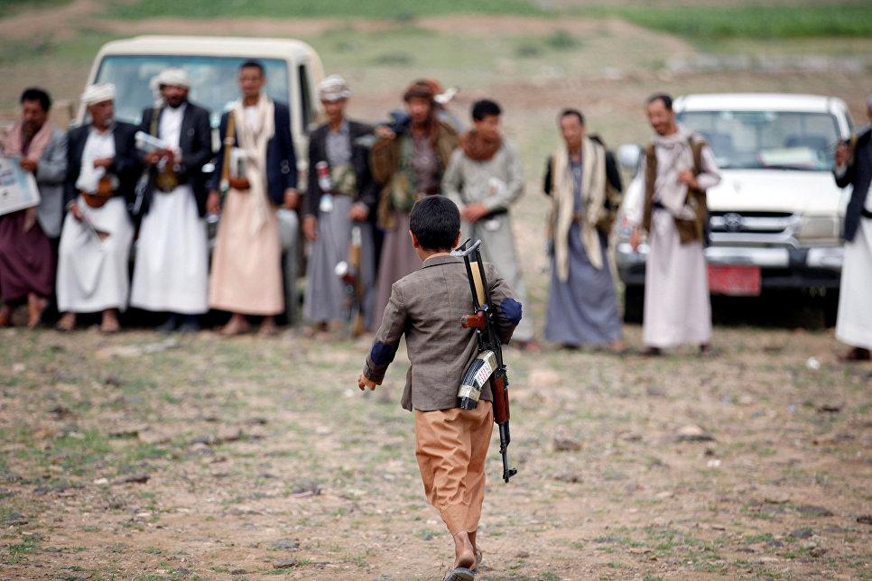 Вооруженный мальчик идет на собрание лояльных по отношению к движению Хути, Йемен. Август 2016
