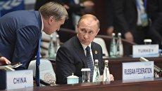 Владимир Путин и помощник президента Юрий Ушаков во время первого рабочего заседания глав делегаций государств-участников Группы двадцати