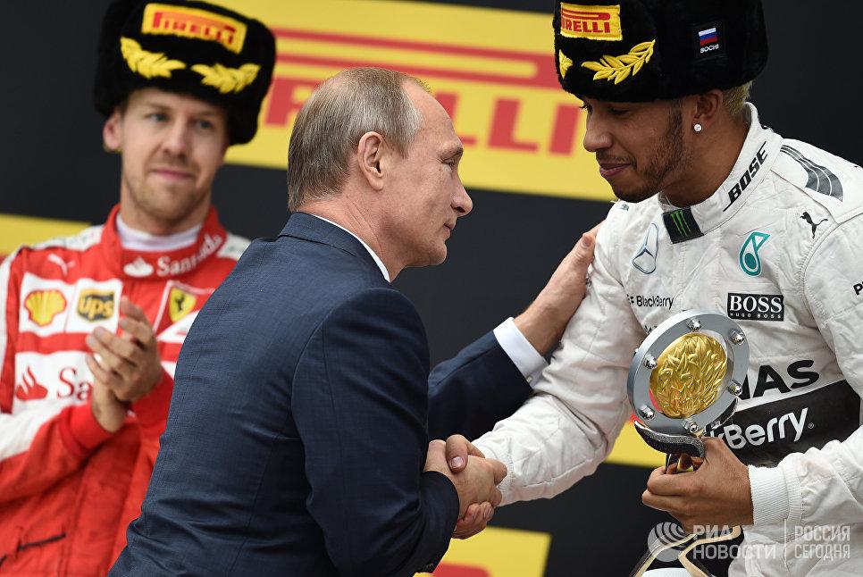 Президент России Владимир Путин вручает Кубок Гран-при России гонщику команды Мерседес Льюису Хэмилтону