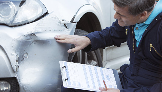Сотрудник страховой компании осматривает пострадавший в ДТП автомобиль