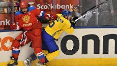 Игрок сборной России Александр Овечкин (слева) и игрок сборной Швеции Антон Строльман в матче группового этапа Кубка мира по хоккею между сборными командами Швеции и России