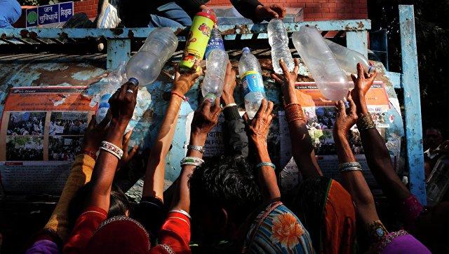 Индийские женщины участвующие в митинге в Нью-Дели, стоят в очереди за питьевой водой
