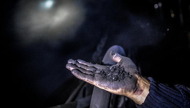 Шахтер показывает уголь. Архивное фото