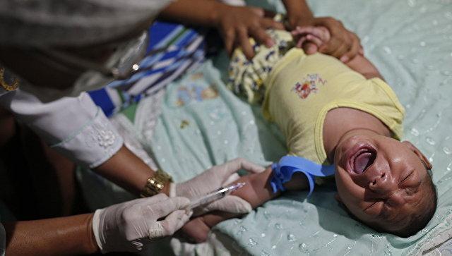 Врач берет кровь у младенца с микроцефалией. Архивное фото