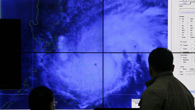 Филиппинские метеорологи смотрят на спутниковое изображение тайфуна Мелор. Архивное фото