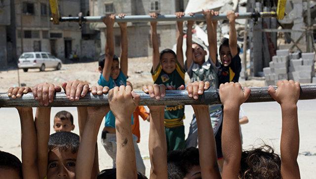 Палестинские дети играют возле разрушенных домов на севере Сектора Газа. Архивное фото