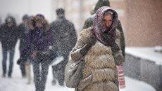 Прохожие на одной из улиц Москвы во время снегопада