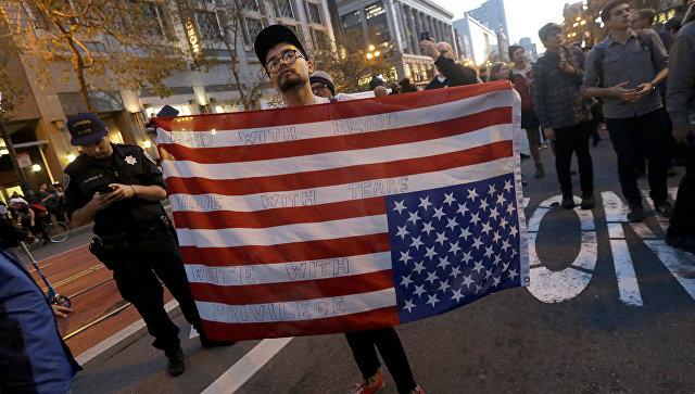 Участник акции протеста против избранного президента США Дональда Трампа с перевернутым флагом США в Сан-Франциско, Калифорния. 9 ноября 2016