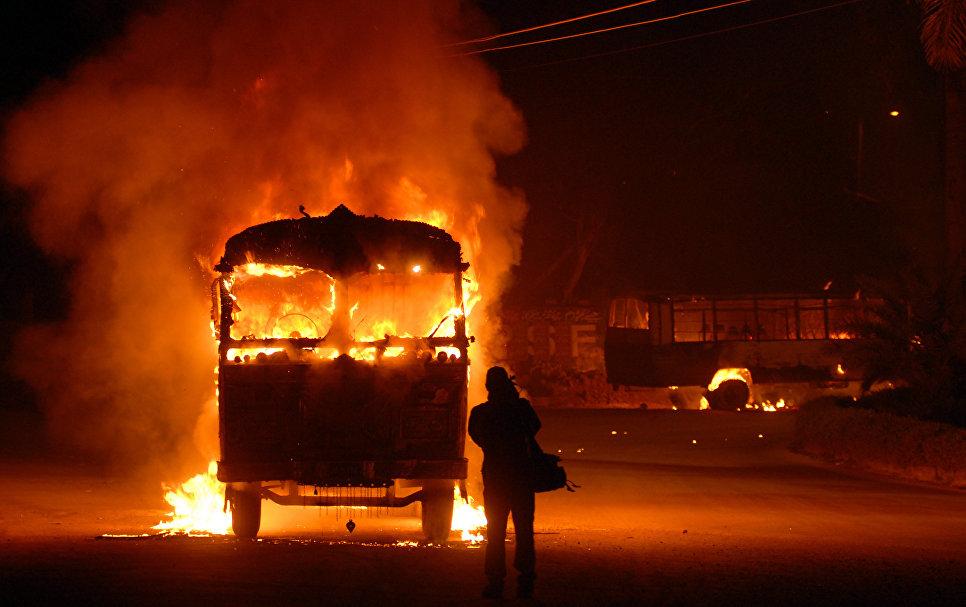 Оператор снимает горящий автомобиль в Карачи, Пакистан
