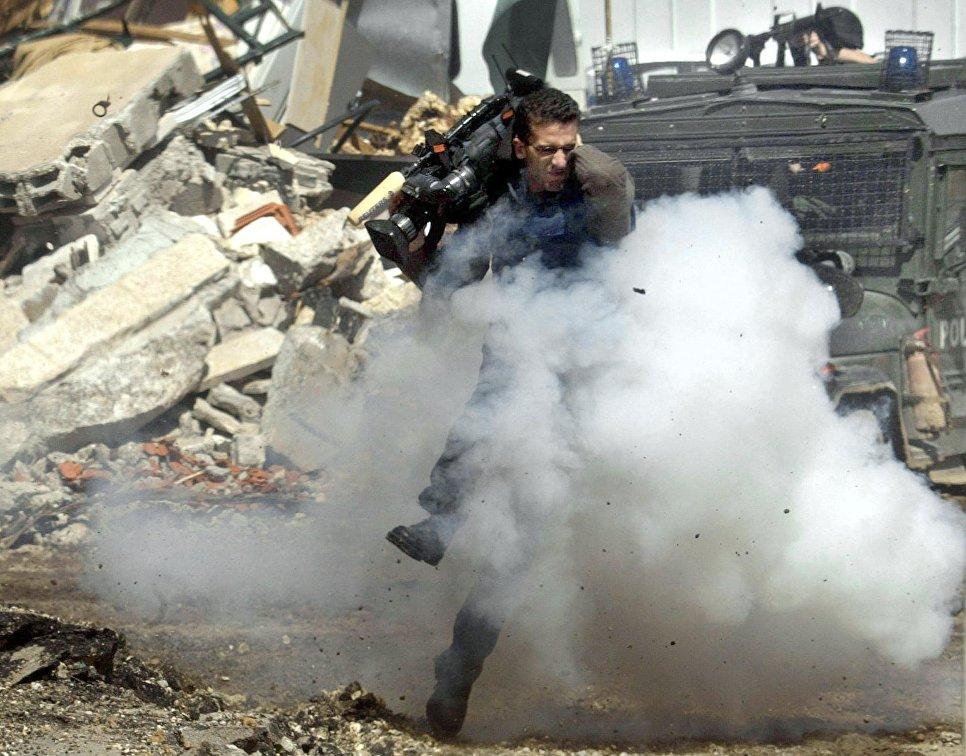 Телеоператор Исмаил Кадер укрывается от гранат в городе Рамалла, 5 апреля 2002