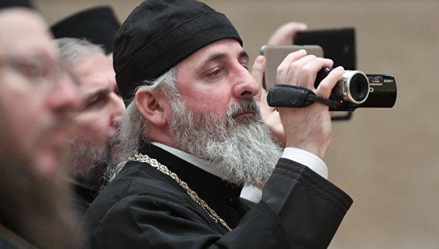 Священник с видеокамерой