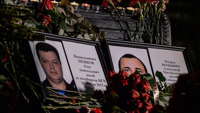 Портреты погибших в Сирии подполковника Олега Пешкова и матроса Александра Позынича и цветы у памятника героям фильма Офицеры. Архивное фото