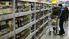 Покупатели выбирают пиво в отделе алкоголя