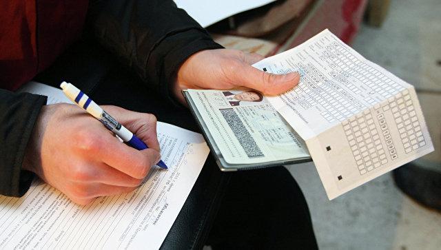 Сотрудник федеральной миграционной службы  проводит проверку документов у иностранных рабочих. Архив
